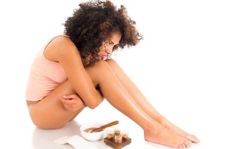 hugging legs: Beautiful young latin woman with silky skin hugging her legs, concept of leg waxing, isolated on white Stock Photo