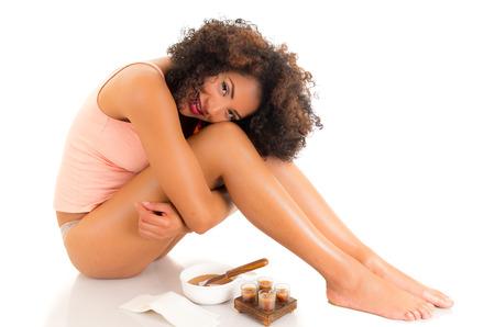 Belle jeune femme souriante latin avec la peau soyeuse étreignant ses jambes, concept de épilations, isolé sur blanc