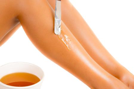 Gros plan de la belle jeune femme latin épilation jambes, isolé sur blanc