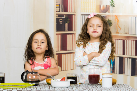 refusing: Two young preschooler girls looking upset refusing to eat their meal