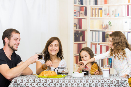dining: Young sweet parents with two little girls having breakfast in the dining room