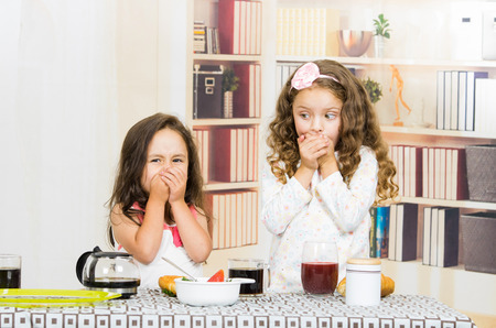 refusing: Two young preschooler girls covering their mouths refusing to eat their meal