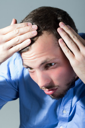 Handsome concerned young man worried about hair loss