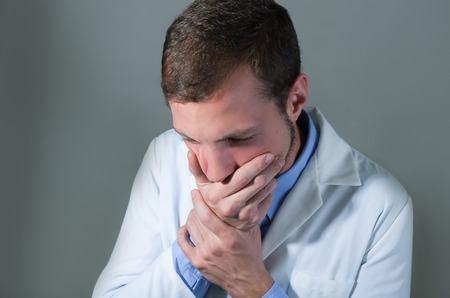 devastated: Closeup portrait of shocked young doctor covering mouth over gray background Stock Photo
