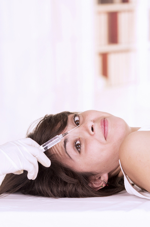 girl lying down: Young girl lying down ready to get a cosmetic botox injection in her face Stock Photo