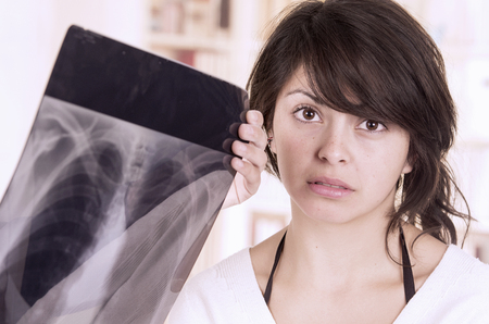 emotional woman: Beautiful young girl looking nervous shile doctor checks xray