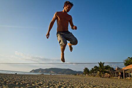 slack: MANABI, ECUADOR - JUNE 5, 2012: Silhouette of young man balancing jumping on slackline during sunset at a beach in Manabi