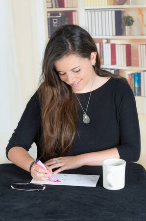head tilted: brunette girl sitting and writing on a paper with head tilted down towards desk with coffee mug