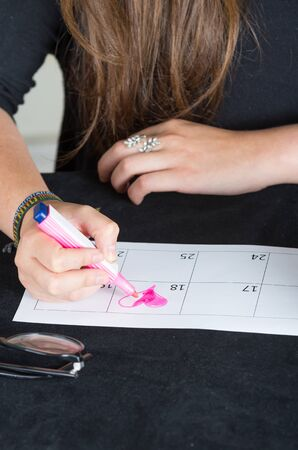 cute lady: closeup of hands drawing a pink heart in calendar Stock Photo