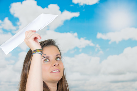brunette holding a paperplane in front of a cloud themed background ready to throw it photo