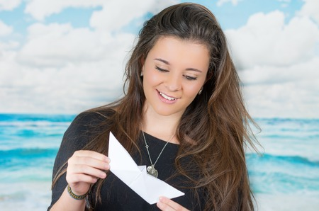 oceanic: brunette holding an origami paper figure in front of oceanic cloud background while looking at the figure