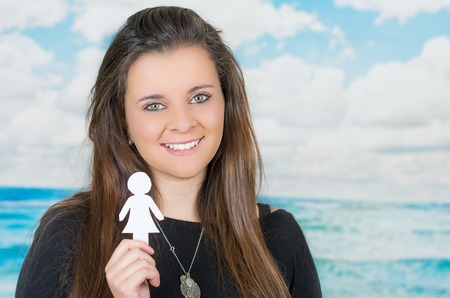 oceanic: brunette holding an origami paper figure in front of oceanic cloud background while smiling