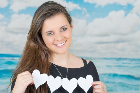 oceanic: brunette holding an origami heartshaped paper figure in front of oceanic cloud background and smiling to camera Stock Photo