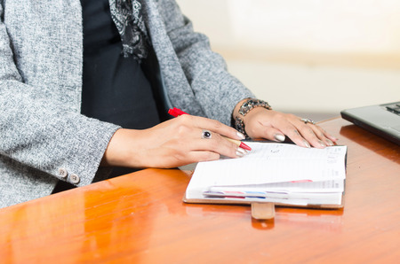 beautiful womb: caption of pregnant womans belly wearing casual clothes at work at desk touching stomach and red pen in other hand