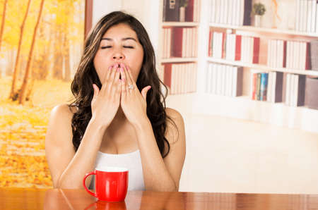 bothered: Female model in tank top early morning yawning and covering mouth with both hands Stock Photo