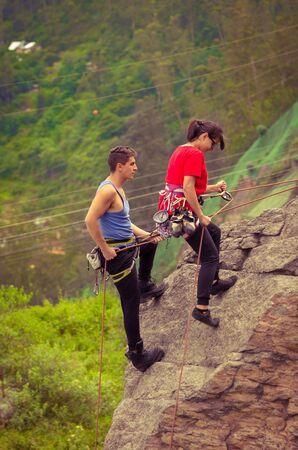 rapelling: man and woman rapelling down mountain in blue and red clothing Stock Photo