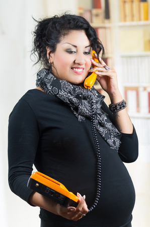 ropa casual: pregnant woman wearing casual clothes talking on landline phone