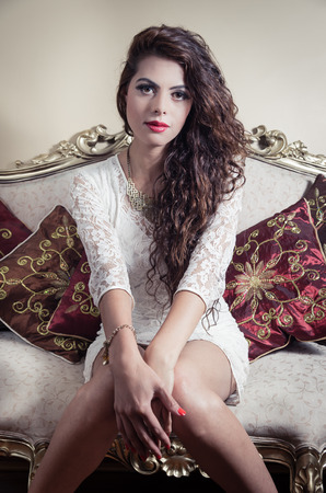 looking into camera: Pretty model girl wearing white dress sitting on victorian sofa looking into camera