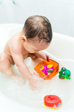 bathwater: Adorable baby boy playing with toys in the bathtub