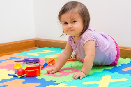 Adorable baby girl playing on child friendly floor mats crawling and looking at camera photo