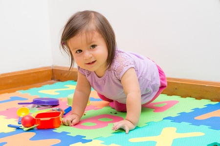 Adorable baby girl playing on child friendly floor mats crawling and looking at camera