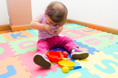 floor mats: Adorable baby girl playing on child friendly floor mats looking down at toys