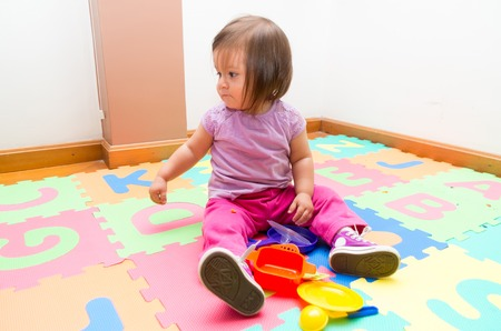 floor mats: Adorable baby girl sitting on floor mats playing with toys and looking to the side