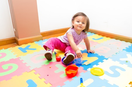 floor mats: Adorable baby girl playing on floor mats and looking to camera