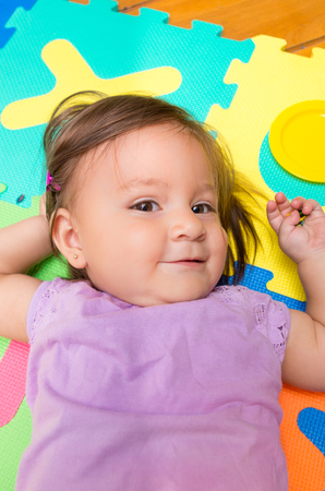 floor mats: Closeup above angle shot of adorable baby girl lying on child friendly floor mats looking up Stock Photo