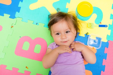Above angle shot of adorable baby girl lying on child friendly floor mats looking up photo