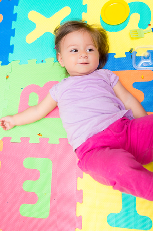 floor mats: Above angle shot of adorable baby girl lying on child friendly floor mats looking up
