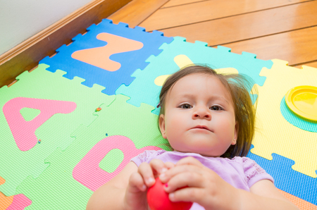 floor mats: Adorable baby girl lying on floor mats and smiling to camera