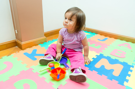floor mats: Adorable baby girl playing on floor mats with colorful toys