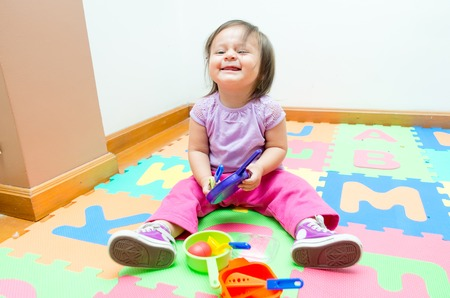 floor mats: Adorable baby girl playing on floor mats with colorful toys and smiling Stock Photo