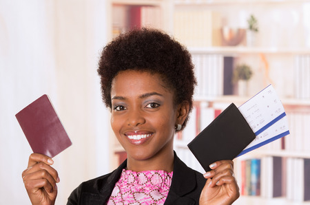 to depart: Black office woman holding up tickets and passport document smiling concept transport airplane airline bus train traveling airport counter depart flight