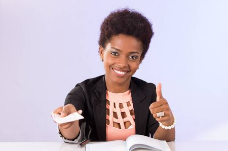black professional: Black office woman sitting by desk smiling and giving document concept transport airplane airline bus train traveling airport counter depart flight Stock Photo