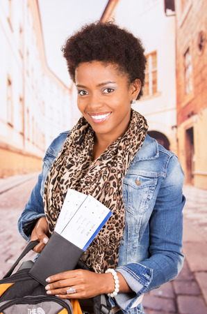to depart: Black woman in casual clothing and bag ready to travel with tickets concept transport airplane airline bus train traveling airport counter depart flight