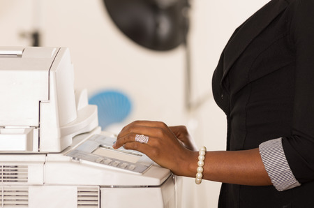 copy machine: Black office womans hand pressing buttons on a copy machine