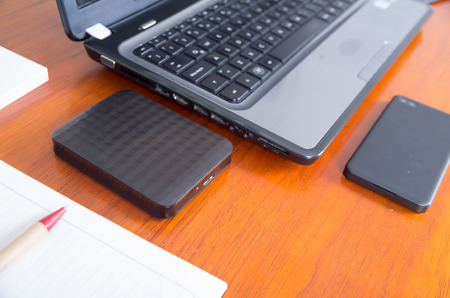 harddrive: Wooden desk with open laptop, cell phone and external harddrive shot from side above angle Stock Photo