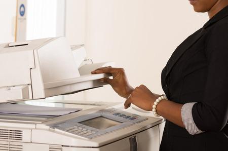 Zwarte kantoor vrouw de hand te drukken knoppen op een kopieermachine Stockfoto - 41686567