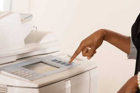 cleric: Black office womans hand pressing buttons on a copy machine