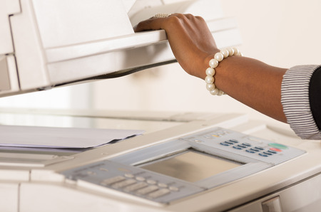 copy machine: Black office womans hand lifting up lid of copy machine