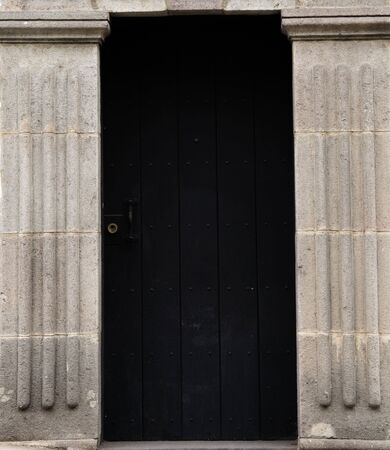 both sides: Ancient style entrance with big black wooden door and big cement poles on the both sides