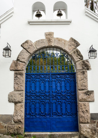 artsy: Artsy blue painted double gate with grey stones forming an arch on white concrete building mediterranean style Stock Photo