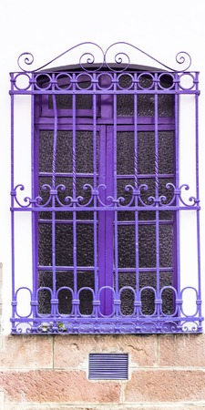 colored window: Caption of purple colored window and metal bars on white concrete building