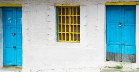 modest: Mediterranean style architecture with yellow metal bars covering window and light blue doors on modest white house Stock Photo