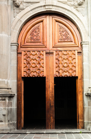 smaller: Giant wooden gate with smaller open doors integrated on massive concrete style building
