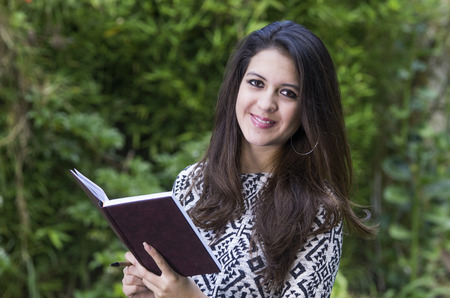 formal clothing: Hispanic brunette in park environment wearing formal clothing holding book open while smiling mouth closed towards camera. Stock Photo