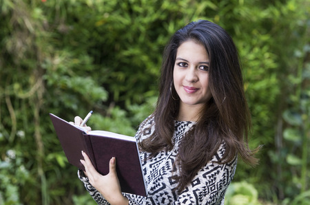 formal clothing: Hispanic brunette in park environment wearing formal clothing taking notes and looking to camera carefully smiling.