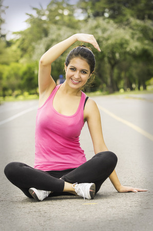 facing right: Hispanic brunette in yoga clothing facing camera sitting with legs crossed and stretching right arm above head smiling.